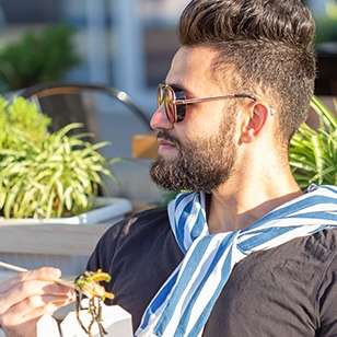 Young man eating food in an outside seating area.