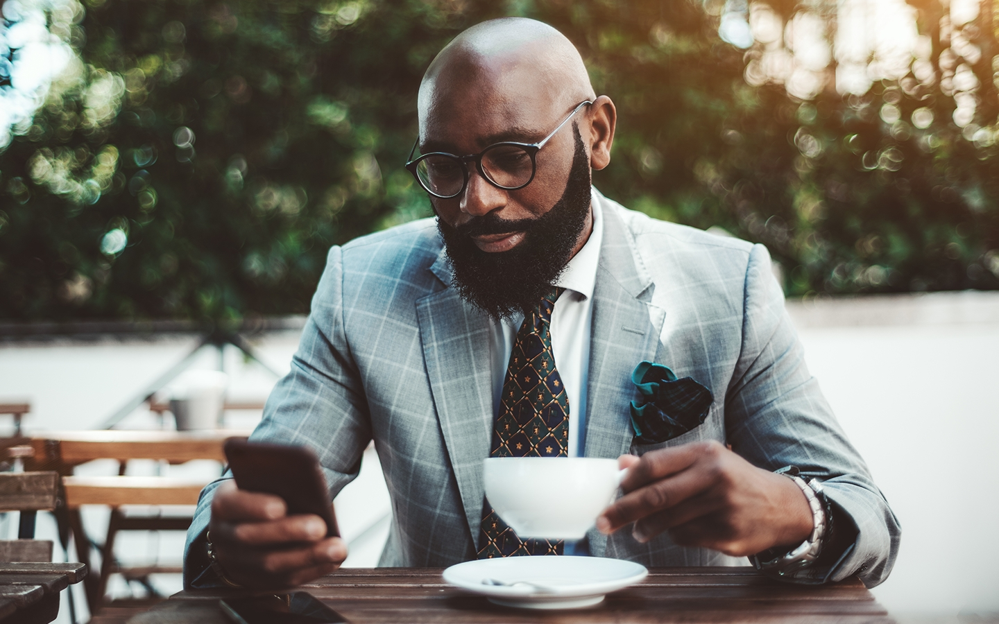 African American man in suit looking at phone over coffee.