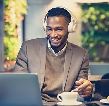 Young man sitting at a table with laptop wearing headphones and drinking coffee.