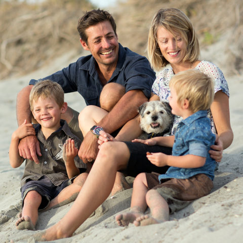 Family of four at the beach, sharing a happy moment together while sitting on a sand hill with their dog
