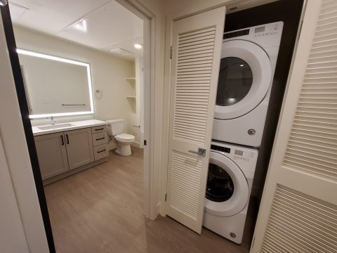 Bathroom with framed mirror and washer and dryer