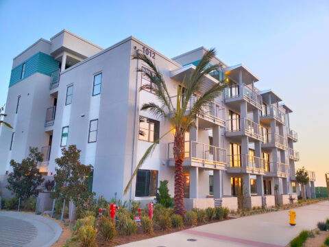 Exterior shot of apartment complex from street view with botanical garden and tropical landscaping