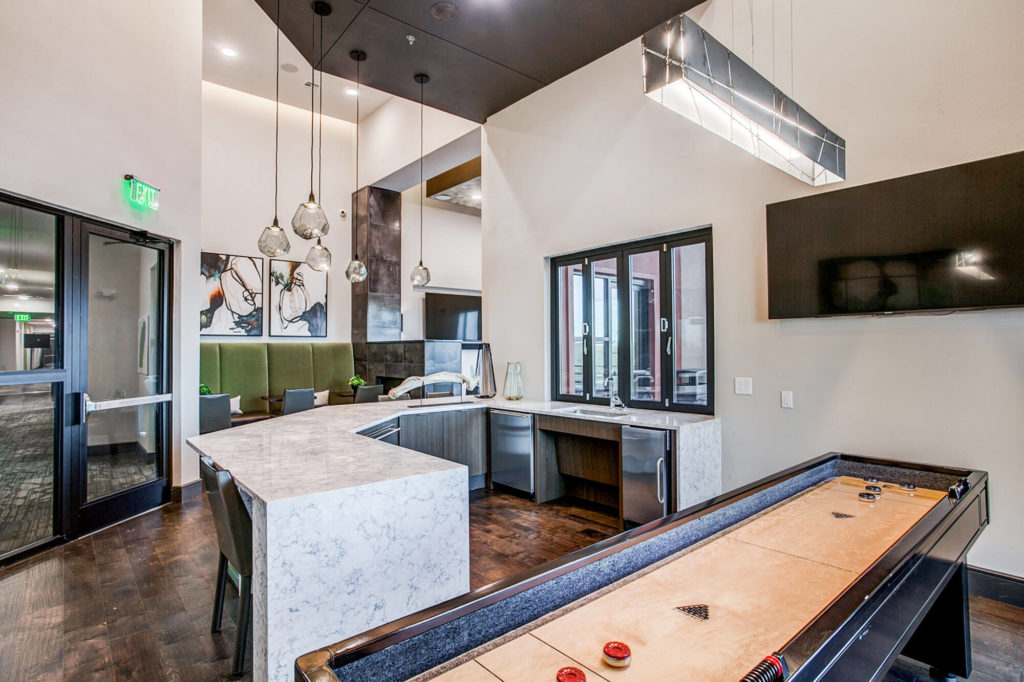 Clubhouse area with large countertop and seating and shuffleboard
