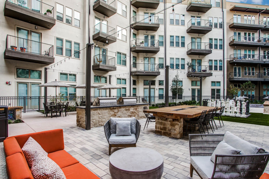 Outdoor community area with grills, plush seating, table seating, patio lights, and life-size chess game