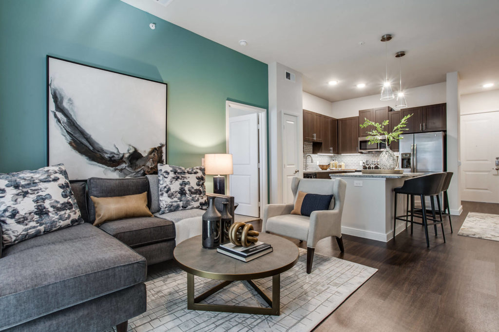 Open concept living room with wood-style floors, teal accent wall, open to kitchen with island, granite counters, and stainless-steel appliances