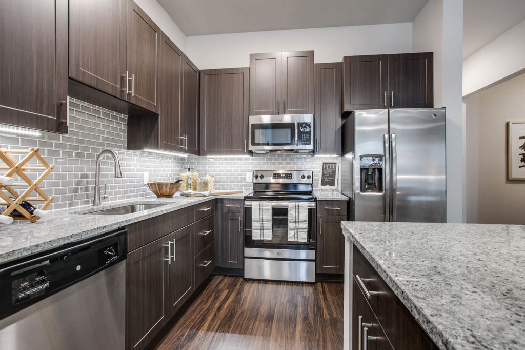 Kitchen with wood-style floors, stainless-steel appliances, granite counters, and stainless single basin sink