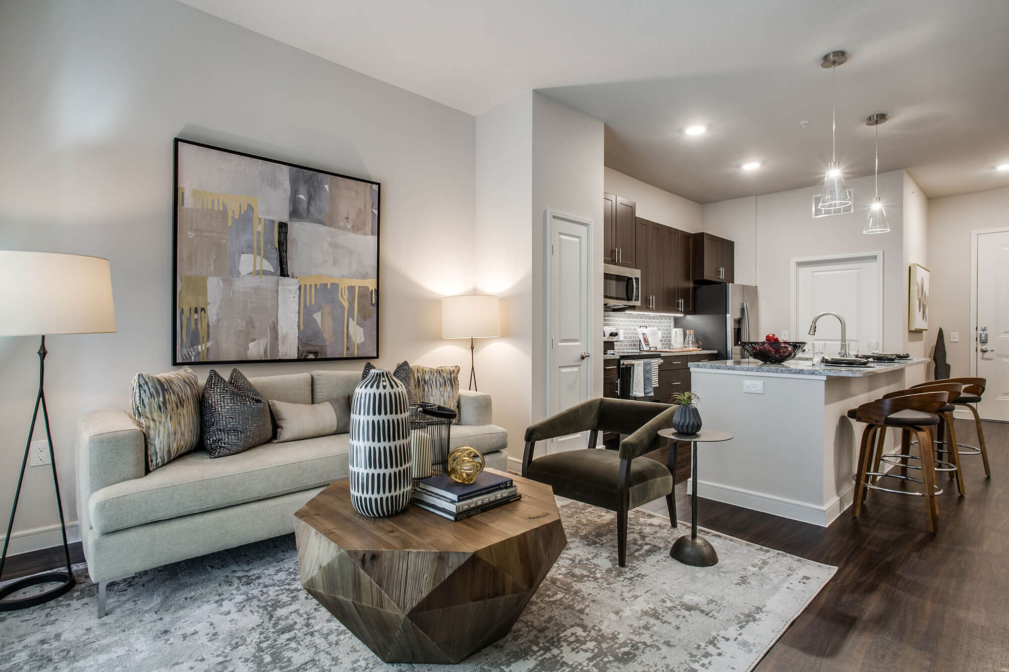 Living room with wood-style floors and modern furniture, open to kitchen with large island, granite counters, pendant lighting, and stainless-steel appliances