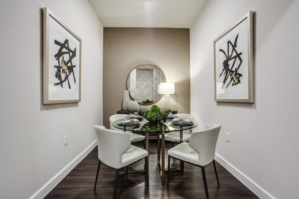 Dining nook with wood-style floors, accent wall, and table with 4 chairs