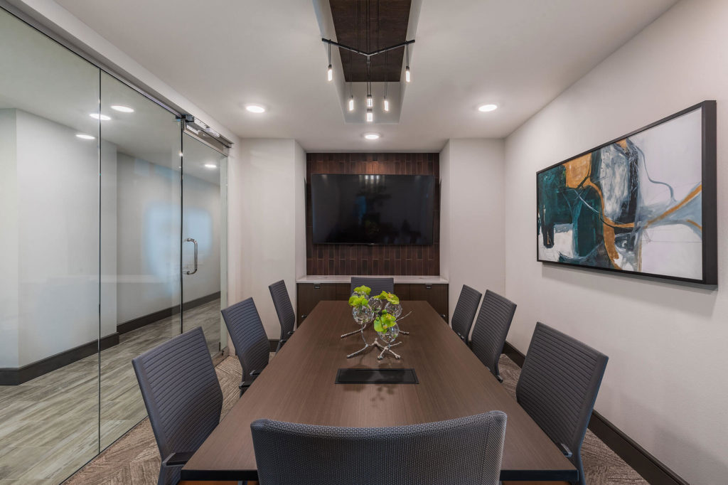 Conference area with long table, 8 chairs, flat-screen tv, decorative lighting and large enclosed glass doors