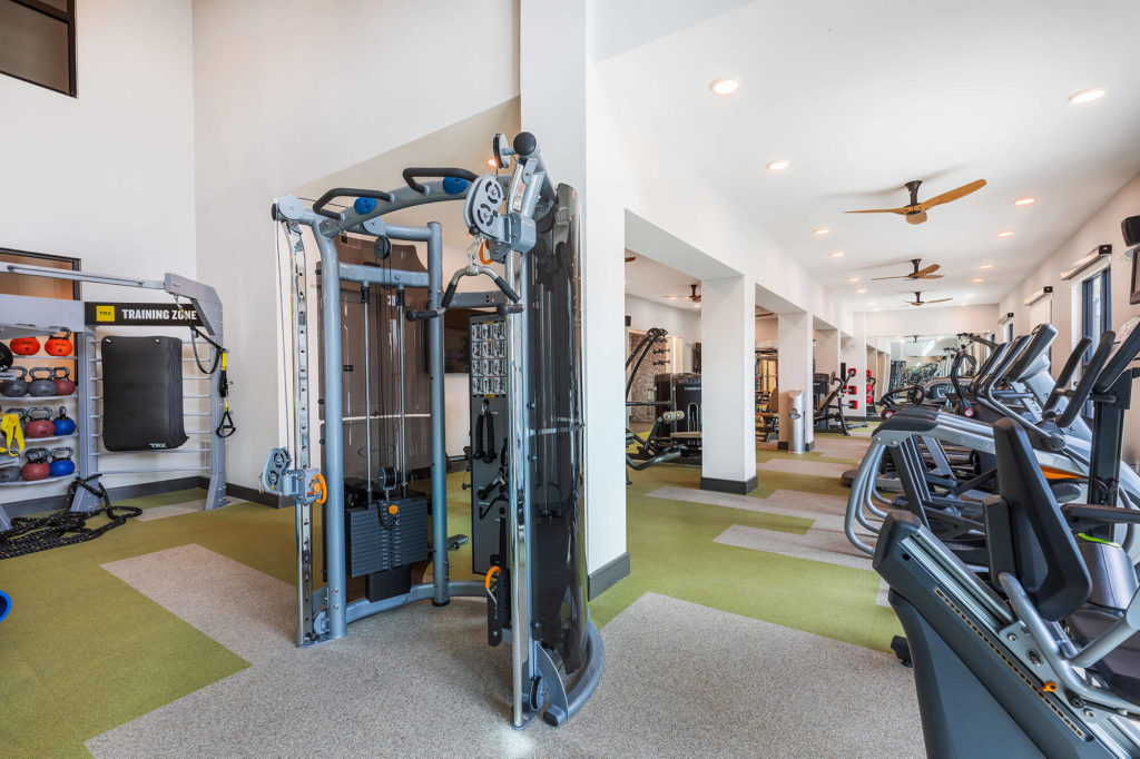 Fitness center with cardio machines, weight machine, kettlebells and ceiling fans