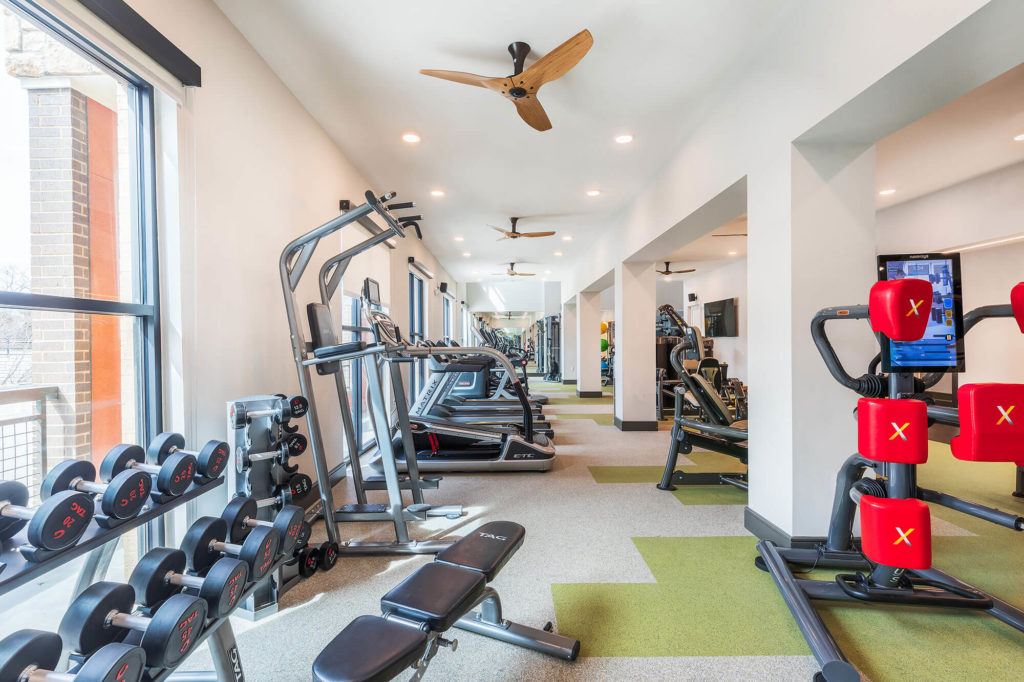 Fitness center with free weights, bench, weight machine, cardio machines, and ceiling fans
