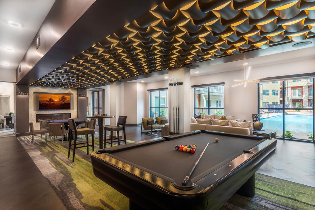 Clubhouse with fireplace, decorative ceiling, pool table, and variety of seating overlooking pool area