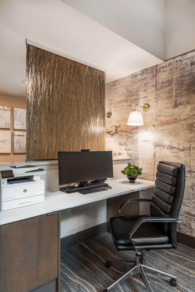 Office space with computer, rolling desk chair, printer, accent wall, and privacy divider