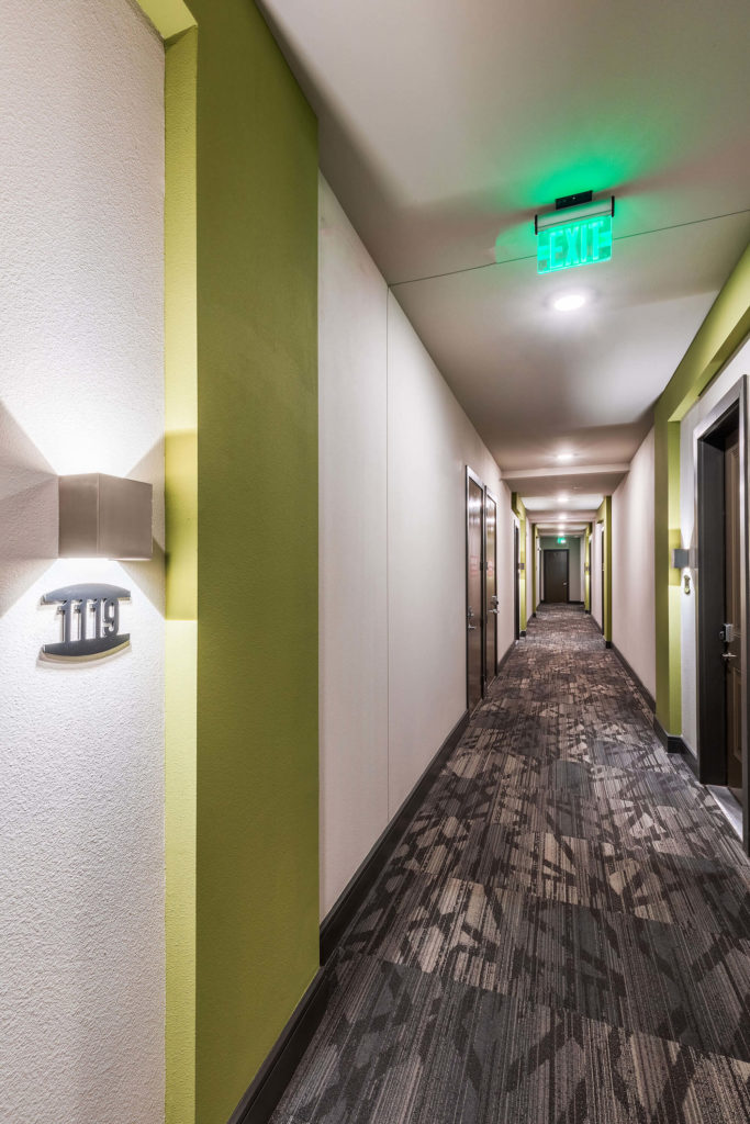 Apartment hallway with exit sign and accent colors