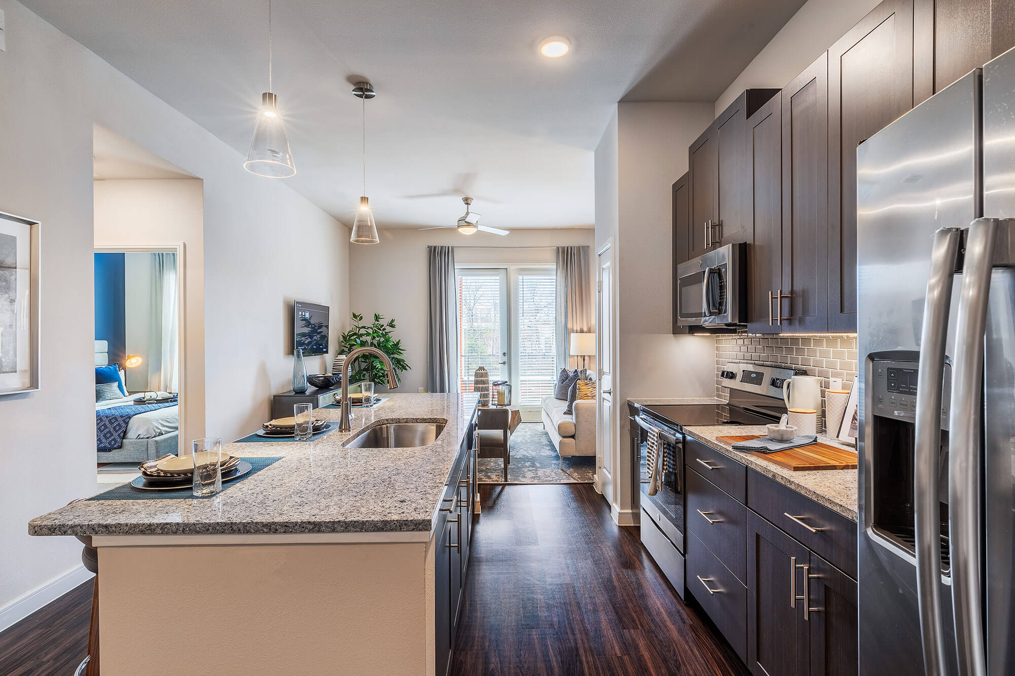 Open concept kitchen with large island with single basin sink, granite counters, stainless-steel appliances, pendant lights which opens to living area with door to patio and hallway to bedroom