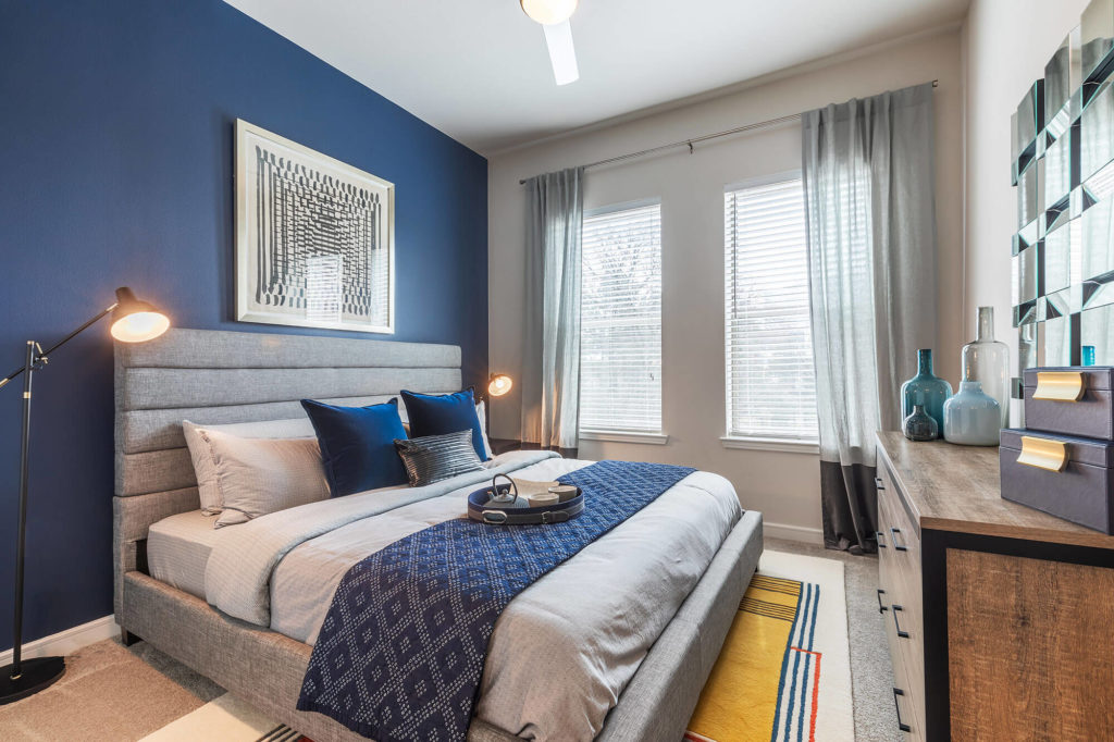 Bedroom with king-sized bed, 2 windows, ceiling fan, blue accent wall, and large dresser