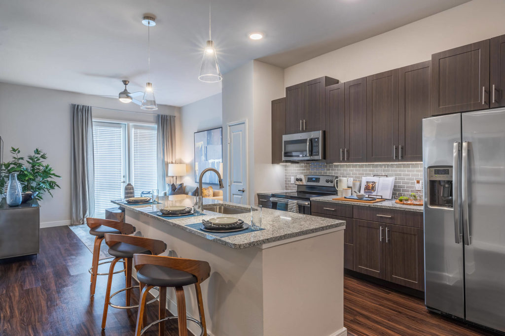 Open concept kitchen and living room with wood-style floors, granite counters, stainless-steel appliances, kitchen island with room for 3 seating, decorative pendant lighting, ceiling fan, and door to patio