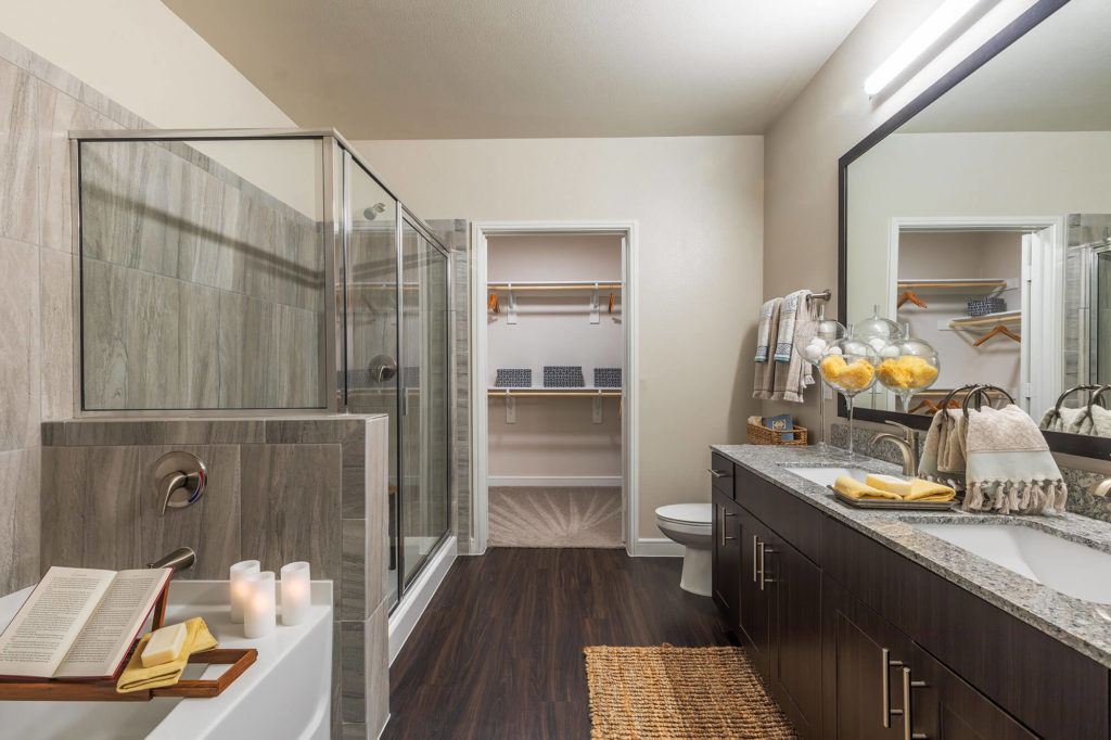 Bathroom with large walk-in shower, soaking tub, wood-style floors, dual vanity, and walk-in closet