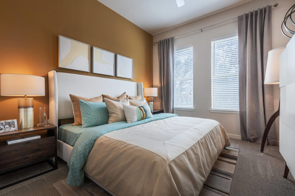 Bedroom with king size bed, plush carpeting, 2 windows, nightstands, and orange accent wall