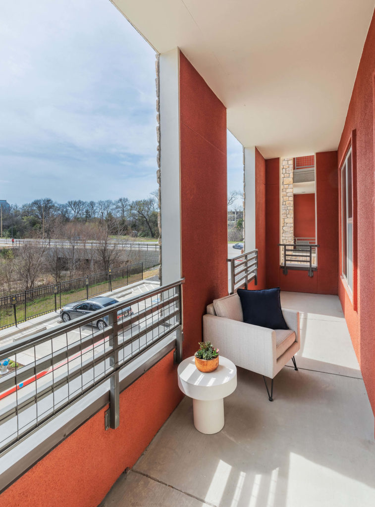 Apartment balcony with table and chair, safety rails, decorative color stucco, and expansive views