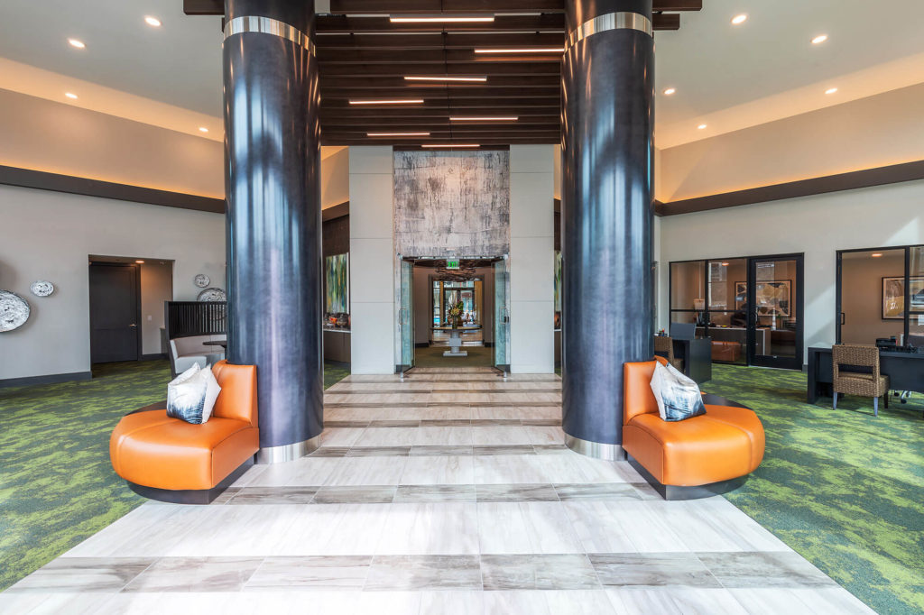 Lobby entrance with decorative pillars, modern furniture, desks and additional seating