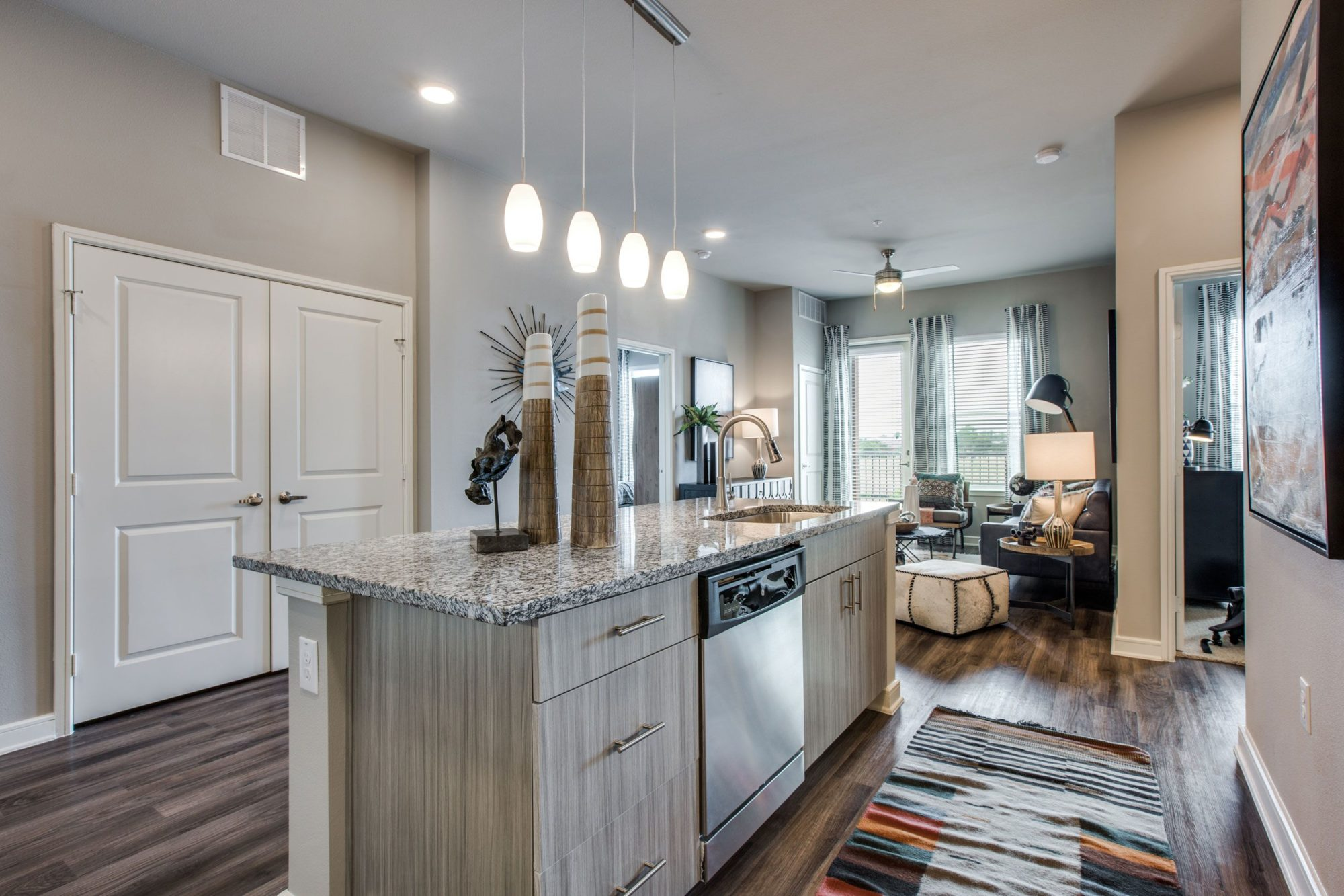 kitchen with island, dishwasher, wood cabinets, wood flooring, granite countertops, and view of living area