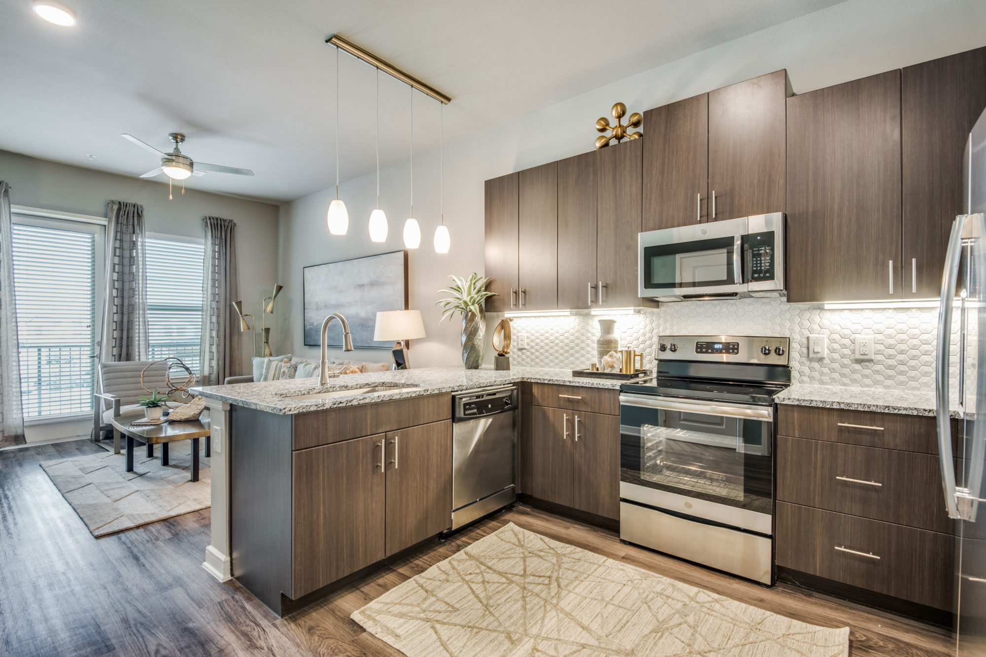 l-shaped kitchen with wood cabinets, stove, microwave, pendant lighting over bar, and single basin sink