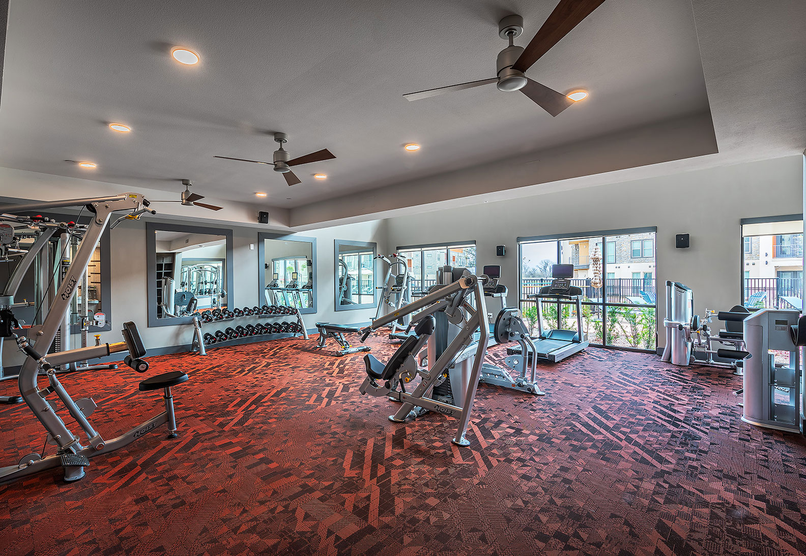 fitness center with free weights, weight machines, and ceiling fans