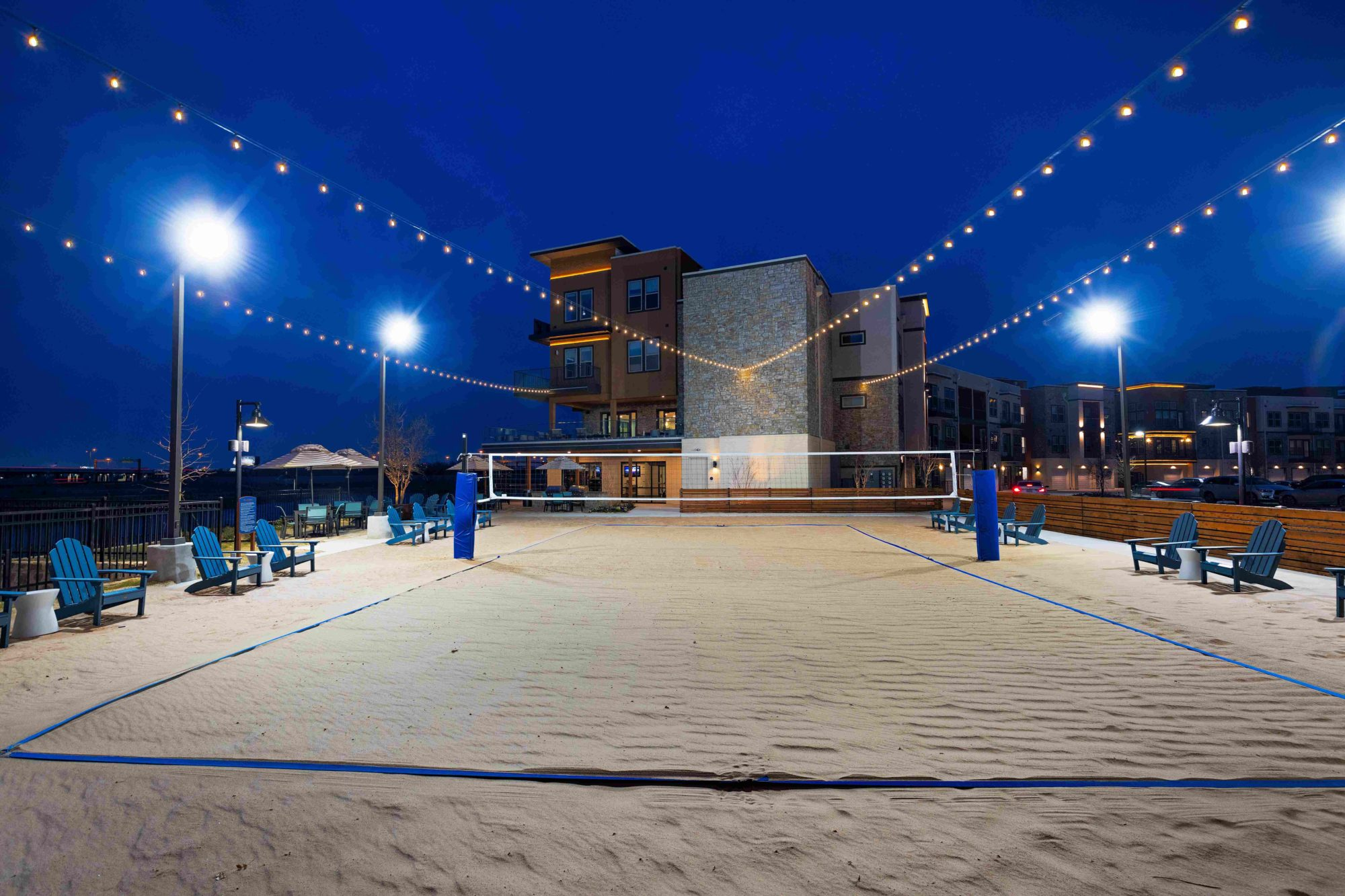 night shot of sand volleyball court with string lighting and property buildings in the background