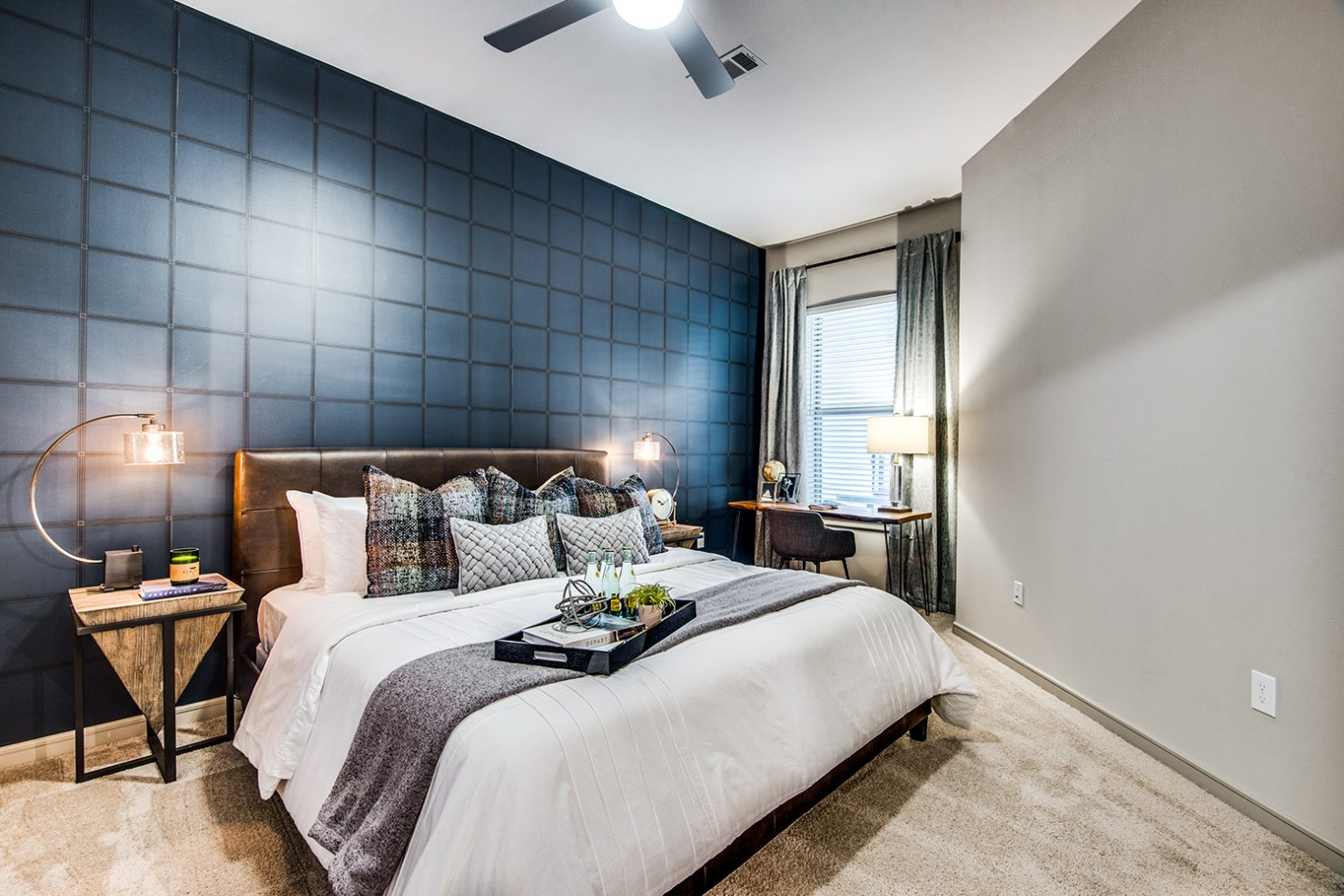 Model apartment bedroom with queen bed, work desk, ceiling fan, and carpeted floor