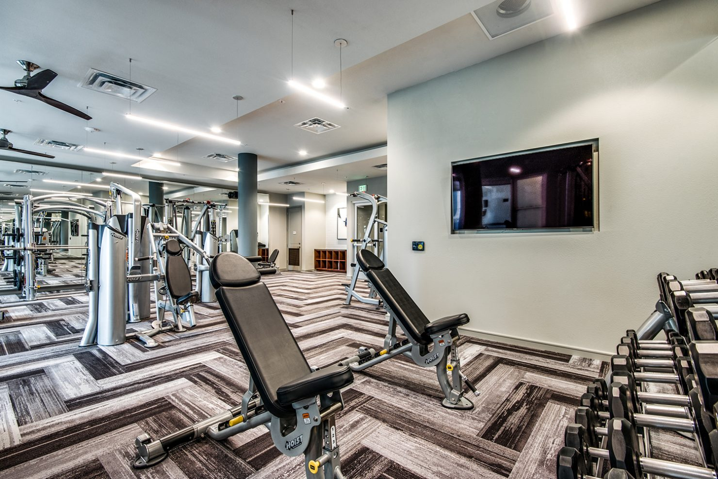 Strength training machines and free weights in community fitness center with wall-mounted TVs
