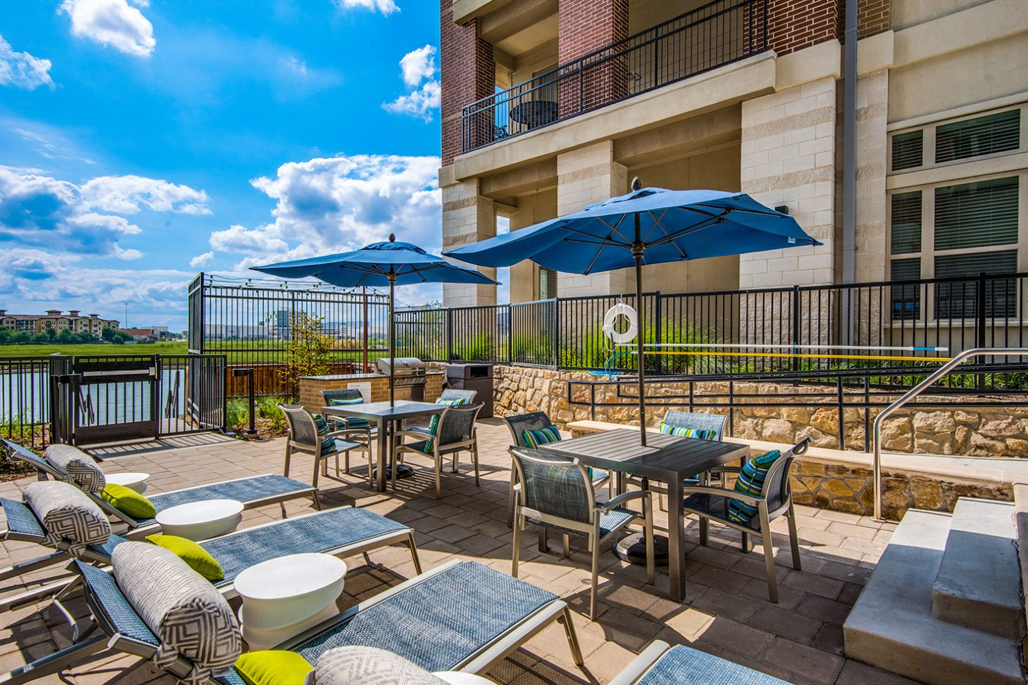Outdoor lounge area with umbrella tables, chairs, and loungers with view of Lake Carolyn