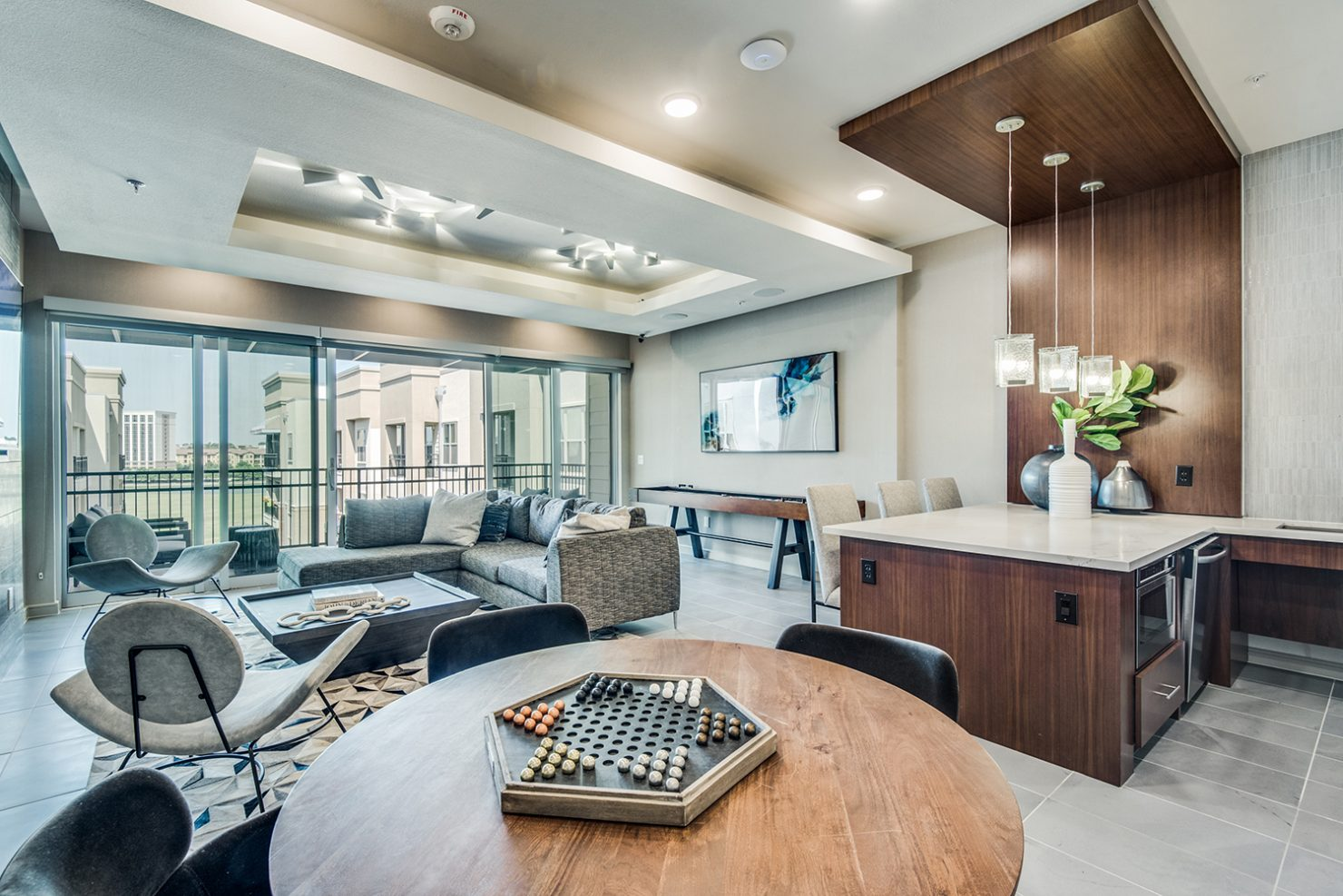 Clubroom with seating area, balcony, shuffleboard, demonstration kitchen, and Chinese checkers