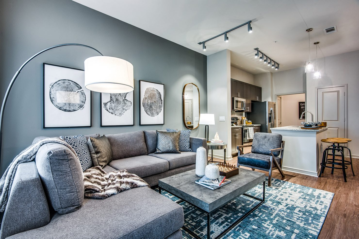 Model apartment living area with large sectional sofa, neutral accent wall, and designer lighting with view of kitchen with island and laundry area