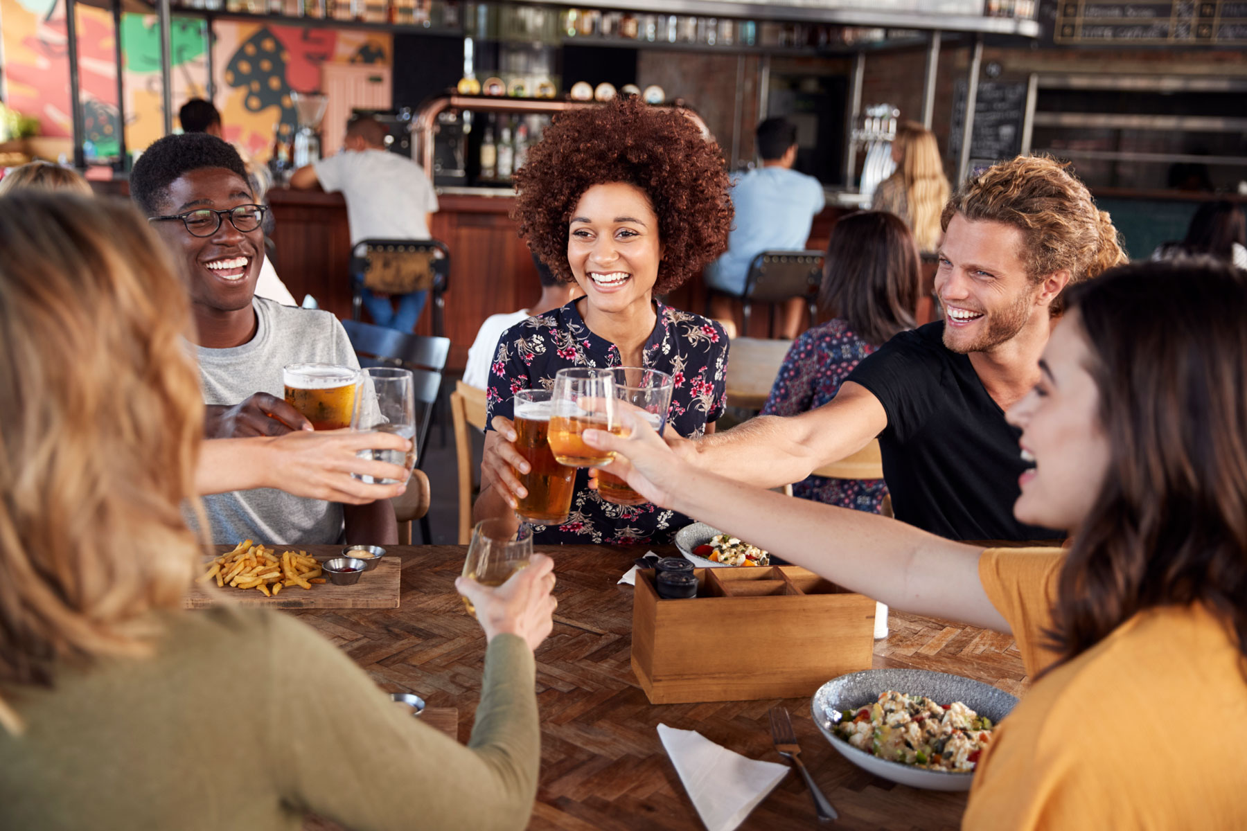 group of diverse young adult friends at local restaurant cheering beers