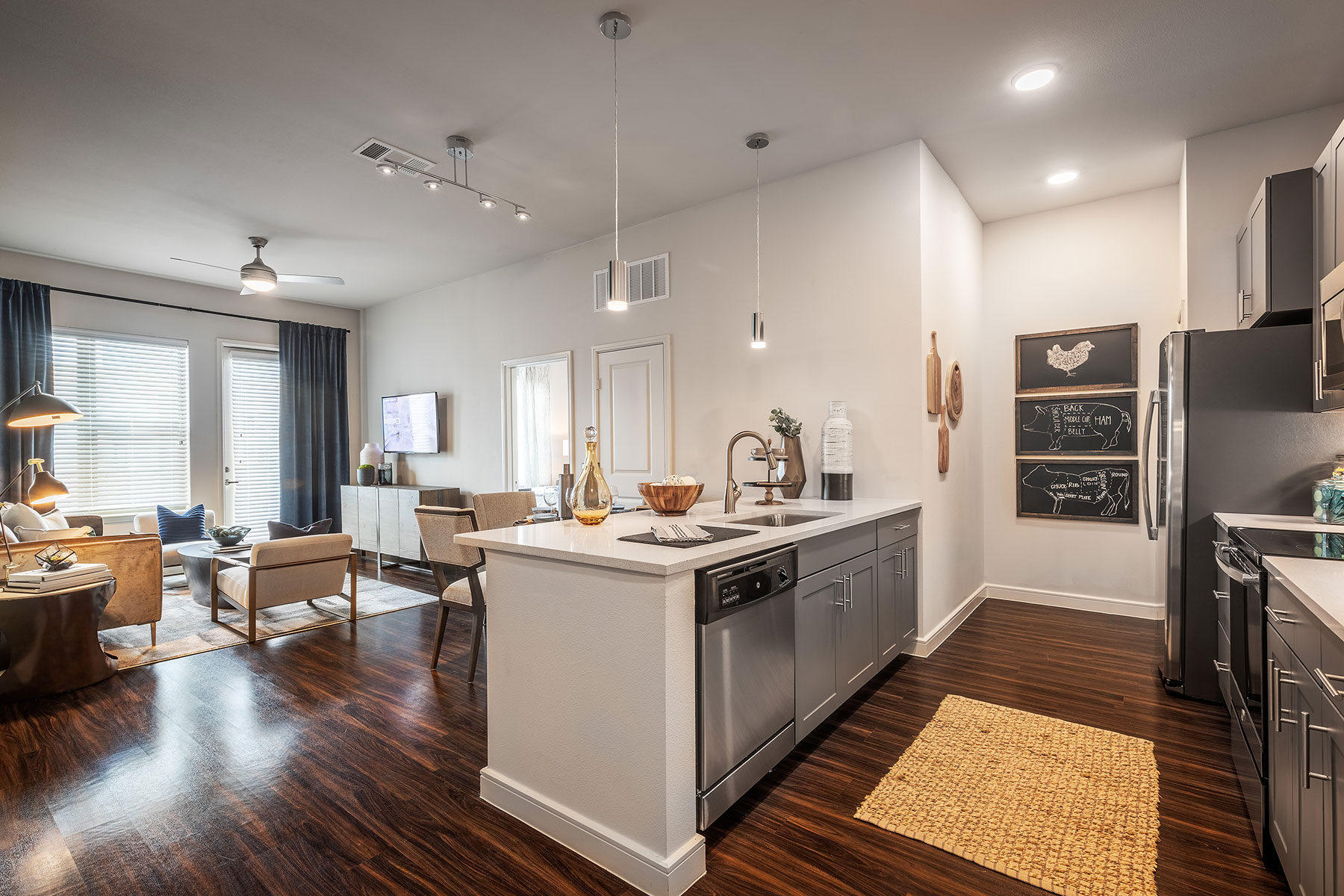 Wide shot of the living area with large windows and comfortable seating, beautiful wooden floor, and kitchen with stainless steel appliances, pendant lights, and farm animal artwork.