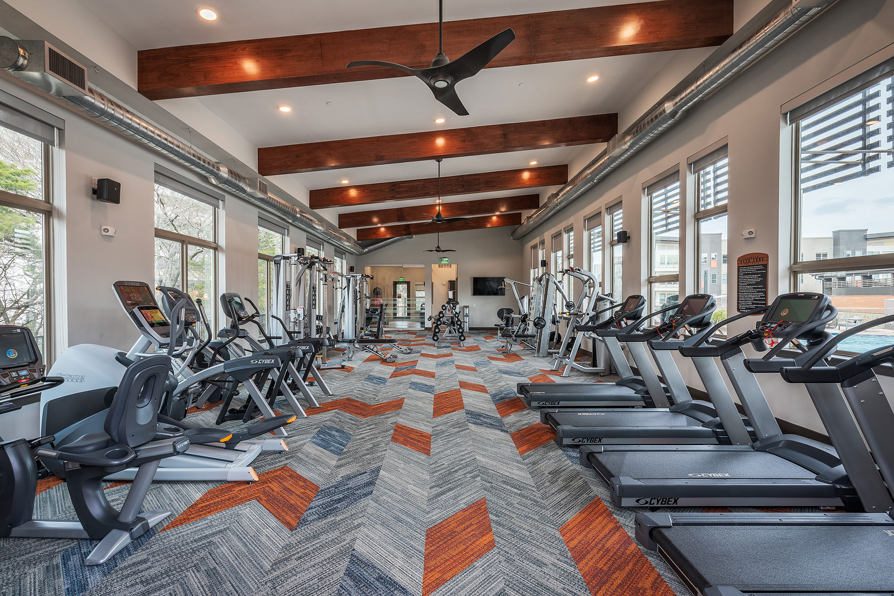Wide shot of the fitness center with a variety of cardio machines, free weights, wall mounted TV and windows outlooking to the pool.