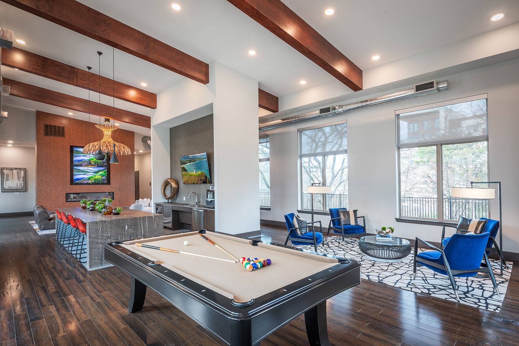 Clubhouse interior with view of bar seating, kitchen area, billiards table and several wall mounted TVs