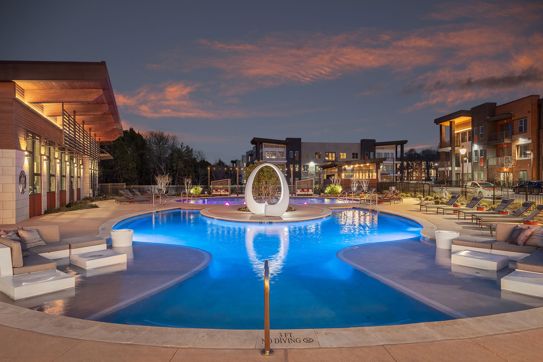 Night time pool shot with oval architecture sculpture, lounge seating, and lighted buildings in the background.