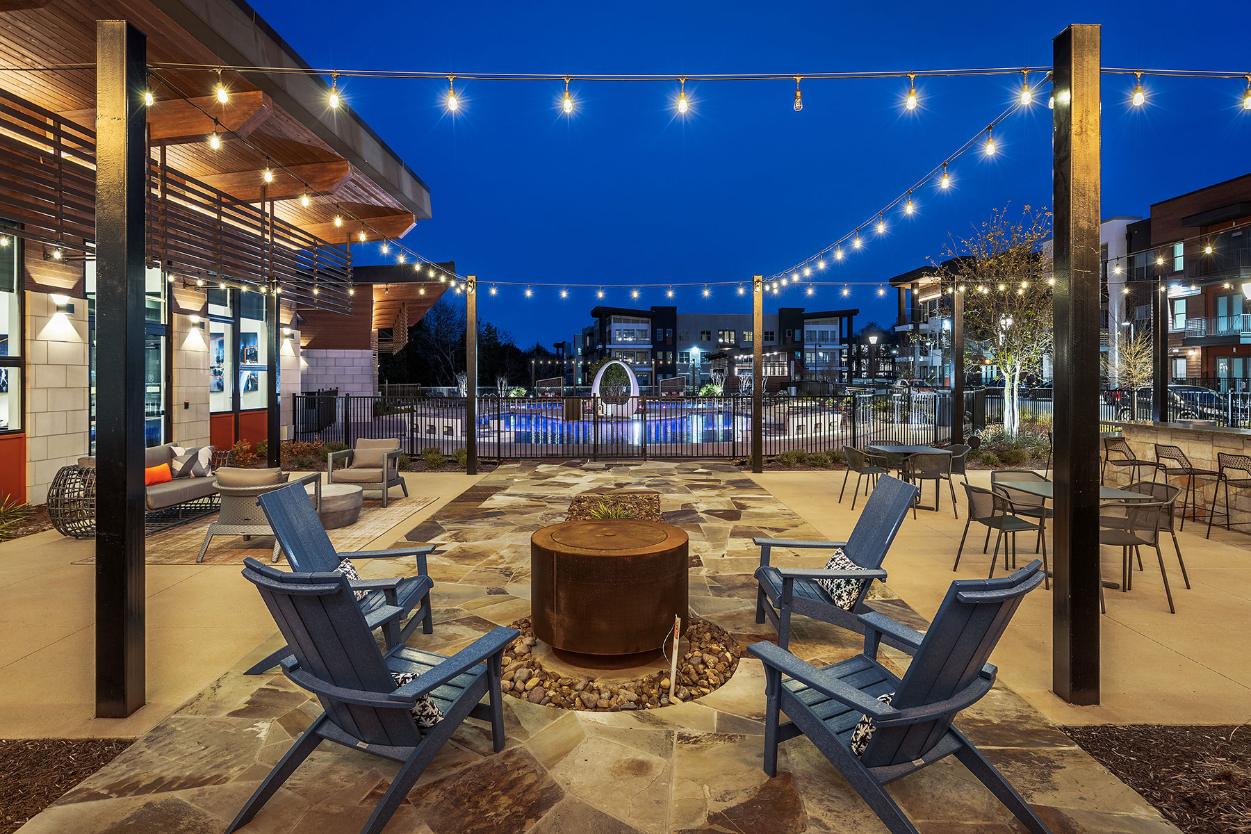Outdoor pool patio seating area with firepit, string lights and view of the pool at night.