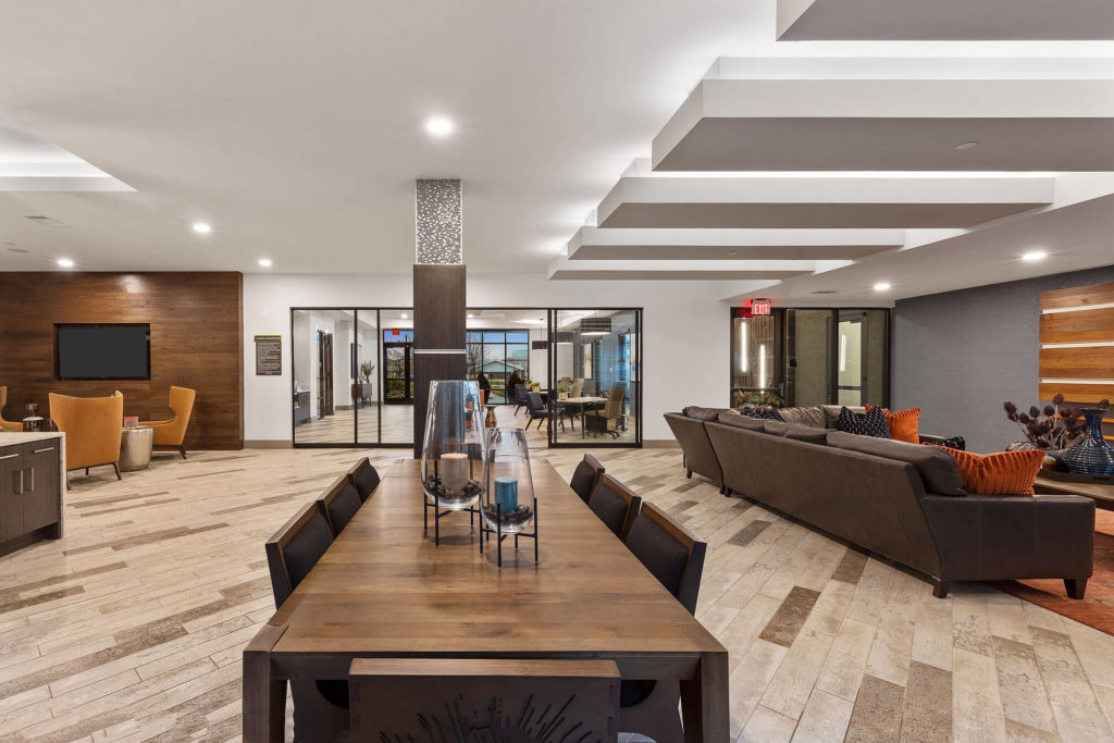 Clubhouse area with long table, lounge seating, and accent wall with flat screen tv