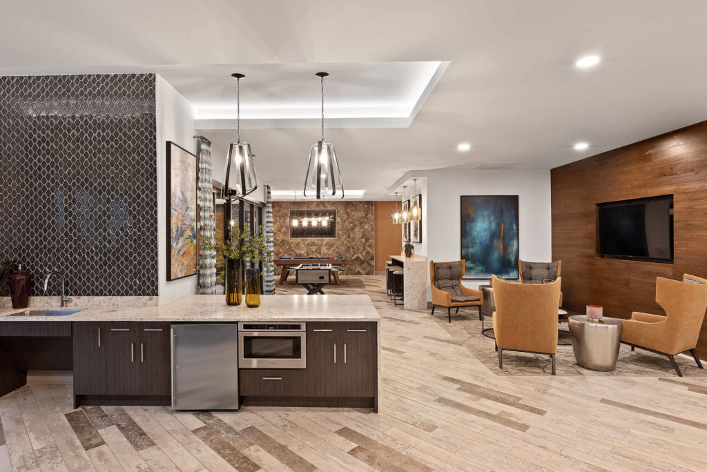 Clubhouse area with lounge area, flat screen TV on wooden accent wall, bar area with microwave, and pool table