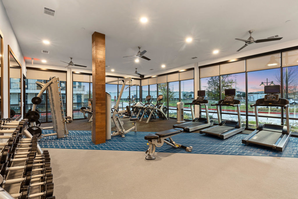 Fitness area with free weight, cardio machines, ceiling fans and floor to ceiling windows