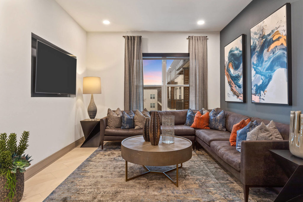 Clubhouse area with large sectional seating, blue accent wall and wall mounted flat screen TV
