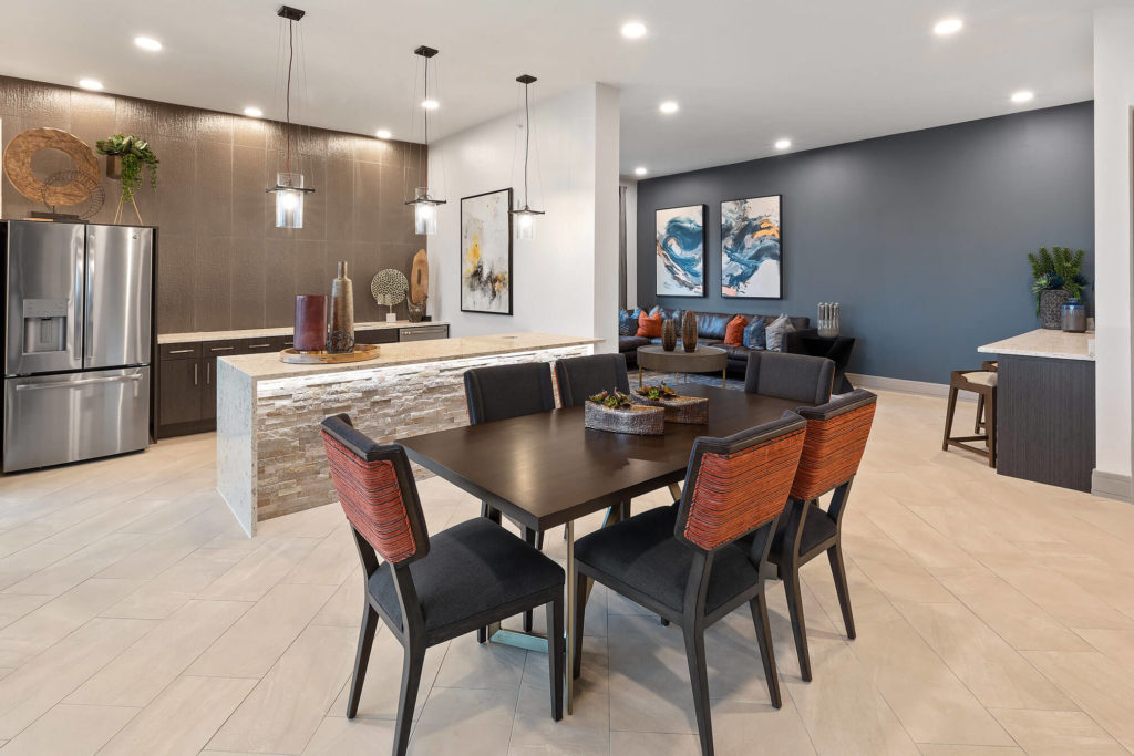 Clubhouse kitchen area with long table, pendant lighting, community fridge and bar area
