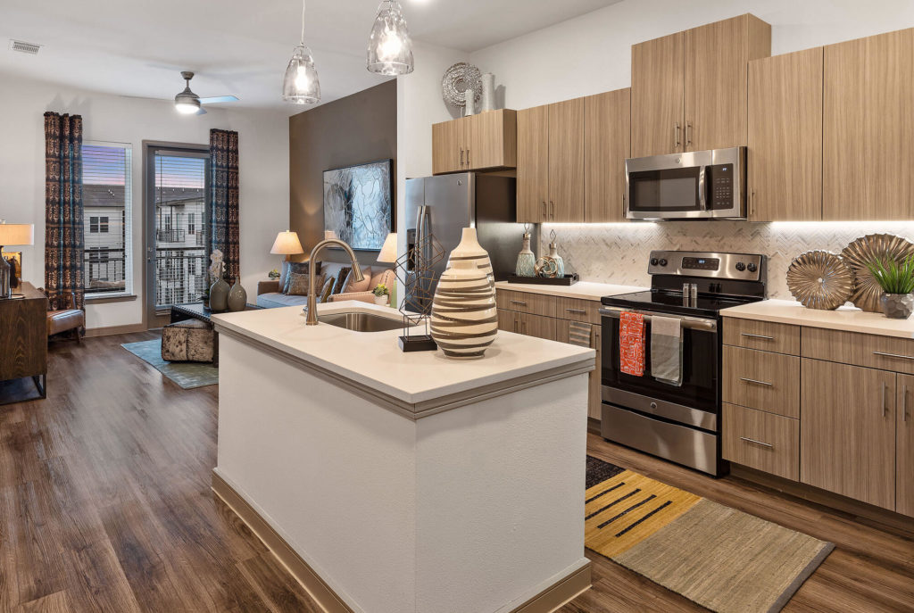 Open concept living/kitchen with wood-like floors, stainless-steel appliances, kitchen island with single basin sink, pendant lighting, living room accent wall, and door to patio/balcony