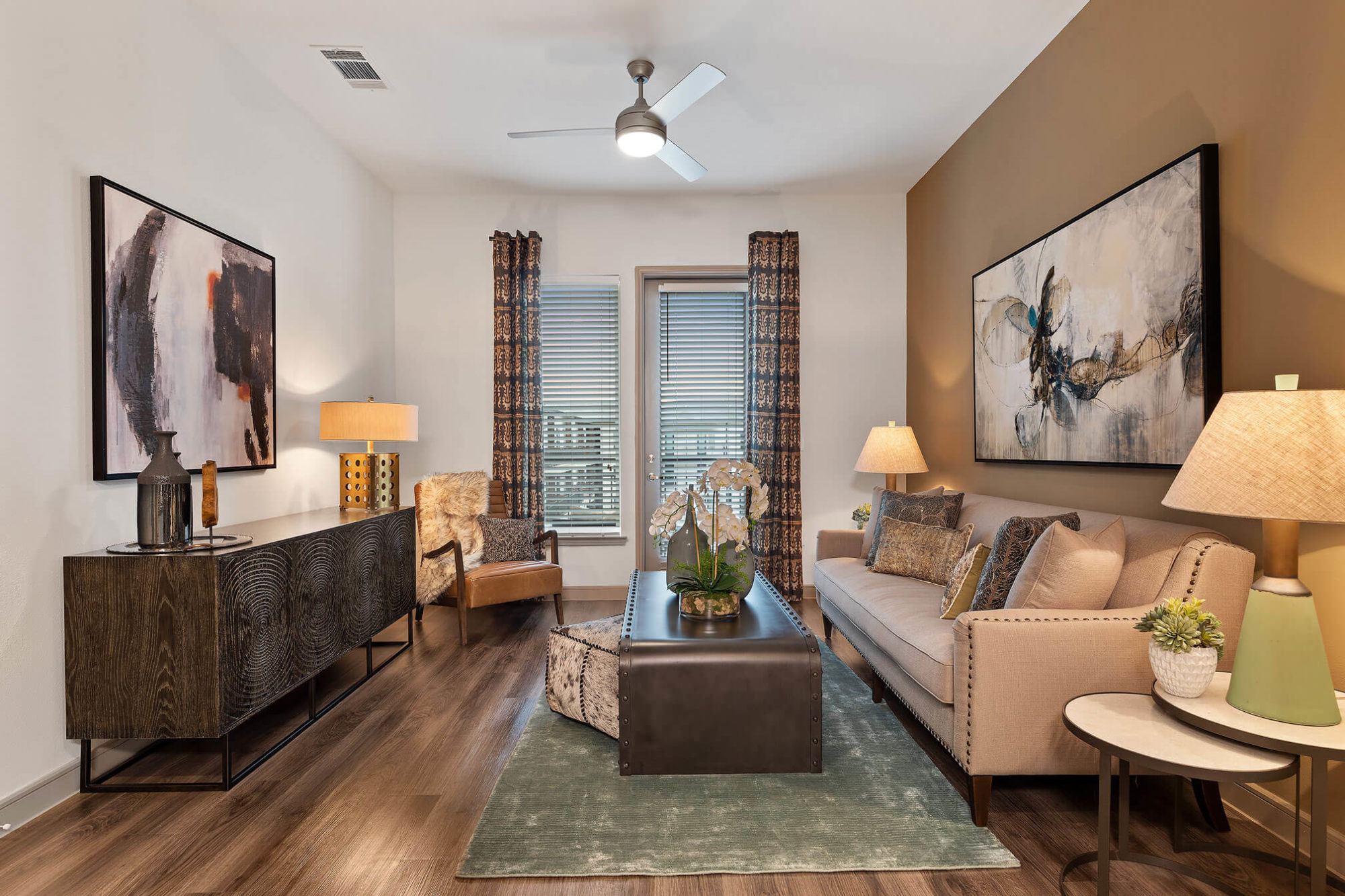 Living room with door to the patio/balcony, wood-like floors, ceiling fan, bronze accent wall and modern furniture