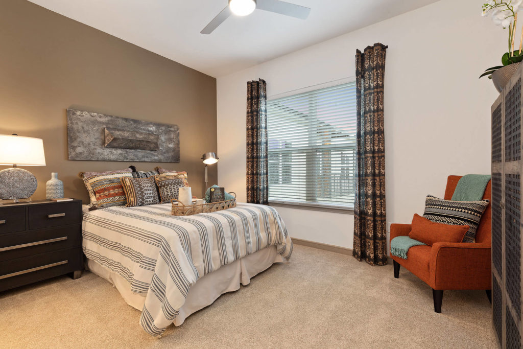 Bedroom with tan accent wall, large window, queen sized bed, large dresser, plush carpet and ceiling fan