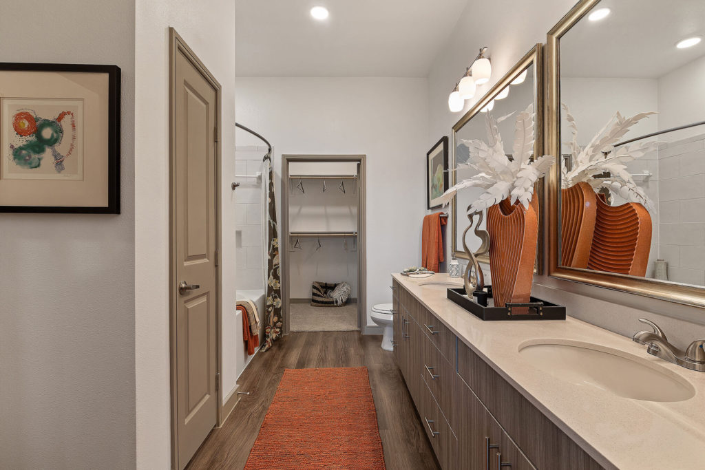 Bathroom with dual sinks, two large mirrors, linen closet, walk-in closet, and large tub/shower