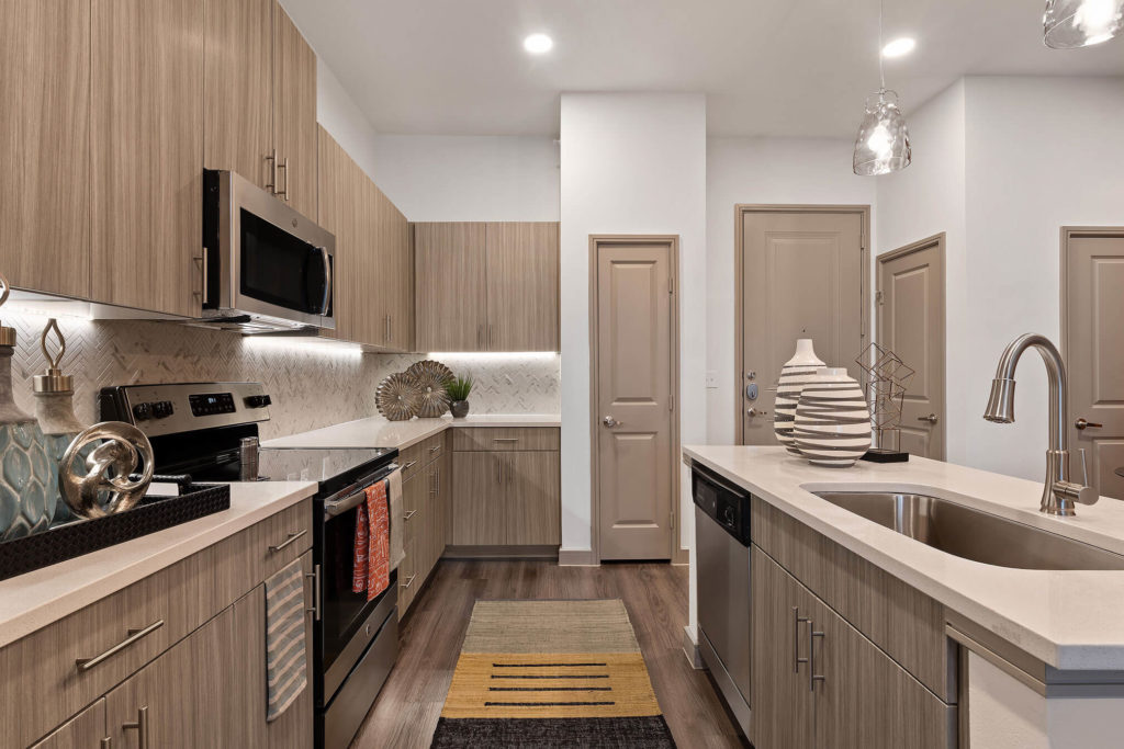Kitchen with wood-like floors, island with large single basin sink, pantry and stainless-steel appliances